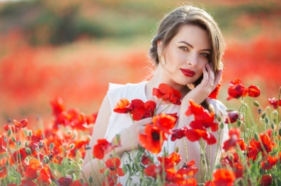 Beautiful young girl with fashion makeup relaxing in field of red poppy flowers, spring time